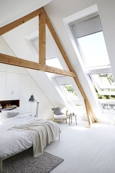 Attic bedroom with lots of natural light, exposed wood beams and white painted floors.