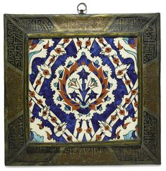 Turkish KUTAHYA POTTERY TILE the tile decorated in underglaze dark blue, turquoise and bole red with black outlines, set into metal frame with calligraphic panels set against painted enamel grounds, framed glazed fritware