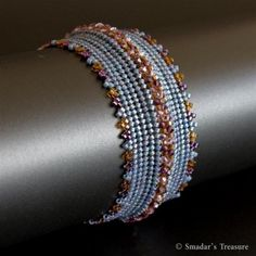 This bracelet is beadwoven with Japanese seed beads in pink luster grayish blue, silver lined burgundy wine and hex-cut amber. A row of sparkling 2.5mm Swarovski crystal beads in amethyst and light amethyst are woven along the center and adding the bracelet more texture, and the alternating colors of the seed beads create triangle pattern along the bracelet's edges.