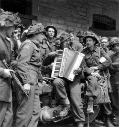 A group of Canadian Highland Light Infantry of Canada of the 9th Infantry Bde 3rd Cdn Inf Div at rest around a Hohner accordion. To the left of the accordionist Lt Jock Anderson, Chaplain of The Highland Light Infantry of Canada.