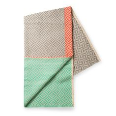 We LOVE this stylish in-house designed throw featuring a woven geo design on a traditional handloom in soft grey, mint green and coral with a frayed edge.