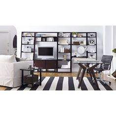 Olin Black Rug, Ripple Black Leather Office Chair, glass top table with saw horse legs, open shelving, sofa with accent pillows