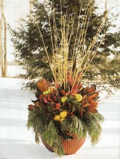 Country goes upscale as green apples and pears are tucked in among magnolia leaves and gold-tipped cedar under a fountain of yellow dogwood twigs. Faux fruit, which is used here, is longer lasting and easier to secure to the arrangement. For the best effect, group the fruit into bunches and layer the foliage for volume.