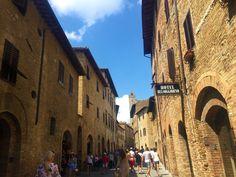 Bekannt ist die Hügelstadt sowohl für seinen Fernblick auf eine idyllische Landschaft mit Weinanbaugebieten und Olivenbäumen, als auch für seine 13 Geschlechtertürme. Die meisten Türme und Bauten wurden schon im Mittelalter errichtet und seit dem 16. Jahrhundert durften keinen neuen Gebäude mehr erschaffen werden. Demzufolge grenzt eine Reise in die historische Altstadt San Gimignano an eine Zeitreise in die Vergangenheit. Siena, Street View, Travel, Time Travel, Old Town, Tourism, Past, Middle Ages, Italy