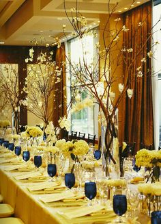 A display of twigs that uses height to its advantage. LOVE this. I like the banquet table setting instead of small round tables.