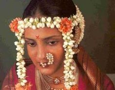 A Marathi Bride. Generally Marathi ladies use this kind of Bindi (बिंदी). The thing she is wearing in nose is known as Nath (नथ). The decorative strings of Jasmine flowers is known as Mundavalya (pronounciation Moondaavalyaa (मुंडावळ्या) ) Probably she is wearing Navuvari Sari (नऊवारी साडी)