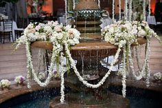 How beautiful the water fountain is dressed with flowers. I love the leis hanging, it brings in all together!