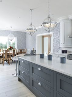 An amalgamation of a contemporary painted and a modern classic. With the quadrant pillars and bespoke curved doors giving a softness to the kitchen.