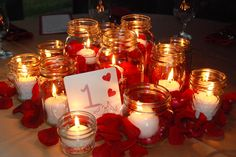 Red and black centerpieces with mason jars | Centerpieces were made up of mason jars, pillar candles, floating ...