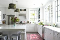 The airy kitchen features marble countertops, casement windows, metal Marais stools, and cup-style cabinet hardware. Textural additions such as peacock-printed lamp shades and a rich red area rug add interest and warmth.