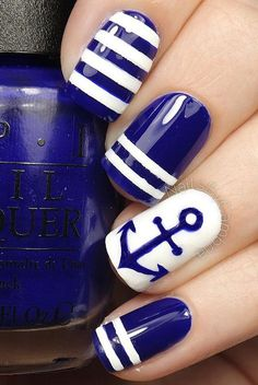 Conquer the anchors with this blue and white nail art design. The nail art is filled with stripes and cute blue anchor painted atop a white polish base color that simple stands out endearingly.