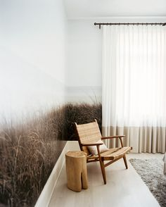 Living Room Photo - Nature-inspired wallpaper in a room with a woven chair and a wood side table.
