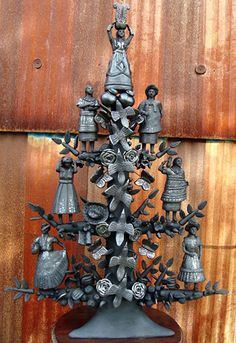 A tree of life sculpture created from Oaxaca's distinctive black pottery. The color results from reduction firing, or depriving the