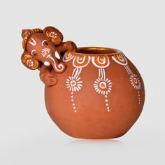 Get this unique terracotta handpainted Baby Ganesha idol crawling on the matki along with the mouse to eat some butter for your home. The baby Ganesha Idol and the Matki has been handpainted with bright colours giving it a class and sheen.