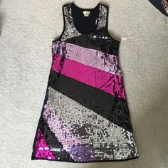 Black racerback flashy dress Bought at a consignment shop locally. Has a tear along seam on back, near armpit, see last pic. Some loose threads too.. Can be repaired easily, I just never got to it. Sequin intact.  Lined. I bought to wear as a shift dress bc I'm usually a size small. Never worn by me, has been hanging in my closet for awhile. Wildcat Dresses Mini