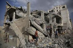 Men inspect a house destroyed by a Saudi-led airstrike in Sana'a, Yemen