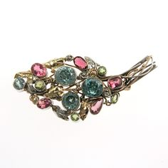 Sibyl Dunlop (attrib.). A sterling silver and 14 carat yellow gold Arts and Crafts floral spray brooch set with blue zircon, pink tourmaline and peridot, c. 1920.