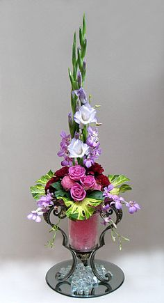 Foliage is Fatsia japonica aurea, & Hedera helix (Ivy). Lilac Gladioli are used to add height..Other flowers used are Lilac Dendrobium orchids (Singapore Orchids), Deep pink Carnations, & Pink Roses - Floral Arrangement by Chrissie Harten / A Flower Arranger's Garden