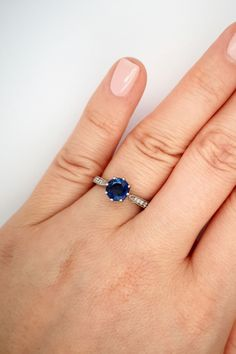 This sapphire engagement ring is set with a 1.20 carat round blue sapphire leading to a tapered diamond-set band. The royal blue sapphire is held in an elegant curtain collet and set with 8 prongs. #LondonVictorianRing #RoyalBlueSapphire #DiamondBand #SapphireRing #SapphireEngagementRing #BlueGemstones Elegant Curtains, Thing 1, Blue Sapphire Rings, Platinum Ring, Blue Gemstones, Designer Engagement Rings, Diamond Bands, Ring Designs, Royal Blue