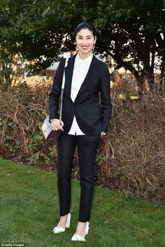 Suited and not booted: Fashion magazine editor Carolina Issa looked elegant in a black sui...