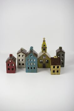 """This set of 6 ceramic buildings make the perfect Holiday village. With holes in the back for candles or string lights, this set is sure to become a family favorite for years to come! church 5.5"""" x 5.5"""" x 12""""tone each design"""