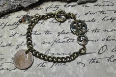 """Steampunk 7 1/2"""" bracelet with hand painted gear links and bronze color curb link chain.  The coin is a 1992 UK One Pence. Attached is a toggle style clasp."""