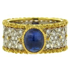 An 18K gold band ring set with a sapphire cabochon (7.2mm x 6mm) and diamonds. The ring size 6 (including sizing balls). Size can be increased by removing sizing balls. Band measures 9.3mm wide and we