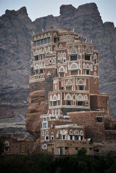 the Dar al-Hajar (Rock Palace) perched atop a rock pinnacle at the Wadi Dhahr Valley in Yemen.