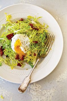 From SAVEUR Issue #168Hailing from Lyon, this French bistro standard gathers a delectable trio of bitter frisée, runny poached egg, and crisp lardons. The salad gets an extra hit of pork flavor from emulsifying the vinaigrette with bacon fat; breaking the yolks into the greens adds even more richness.