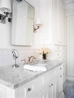 It's the small details like simple sconces, delicate molding and a marble countertop that make this bathroom the elegant space it is.