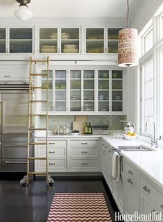 Instead of cutting off cabinets when it gets to a height you can't reach, use a ladder to stack 'em as high as the ceiling. Designer Katie Ridder opted for one on a rail, so homeowners can push the steps across the room with ease.