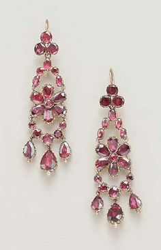A PAIR OF ANTIQUE GARNET EAR PENDANTS   Each circular-cut garnet trefoil motif, suspending oval-cut garnet lines, by a pear and circular-cut garnet floret, to the graduated circular-cut garnet swag, enhanced by three pear-shaped garnets, with closed back, mounted in gold, circa 1830
