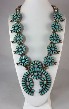 """Size matters!  This turquoise squash blossom necklace is the largest we have had.  The naja is 5 1/2"""" tall by 4 1/2"""" wide, each cluster is 1 1/2"""" wide by 1 3/8"""" tall, plus the blossom.  For a very important person to wear, the total length stretched out is 37"""". Length is 21"""" from top to bottom of naja."""