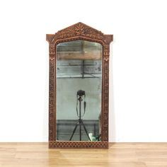 This accent mirror is featured in a solid wood with a rustic dark wood finish. This bohemian mirror has a pointed top with leaf motif accents and intricate carved trim. Great for decorating a hallway! #bohemian #decor #mirror #sandiegovintage #vintagefurniture