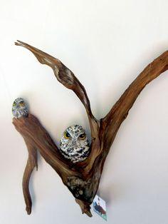 stone owls on driftwood