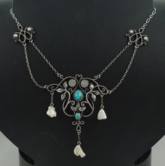 Arts & Crafts necklace (attributed) Arthur and Georgie Gaskin, c1910. Silver swagged pendant necklace, circa 1910, in the manner of Arthur and Georgie Gaskin, with its typically Gaskin-like bar twist heart sections, leaves and tendrils. The necklace is set with cabochon turquoise, mother of pearl and blister pearls. It is 15.5 inches in length and the central stone-set section is 1.5 inches wide and 2.5 inches long from the top of the drop to the bottom of the cen