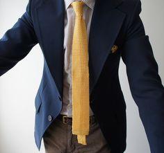 Navy sport coat, check shirt, yellow knit tie, brown pants