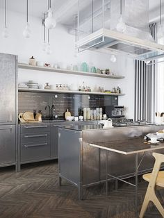 Stainless steel kitchen, warm herringbone wood floors, white walls
