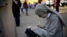 A nun writes notes in the area around the ancient Colosseum a few hours ahead of the Way of the Cross procession, in Rome, Friday, April 14, 2017.