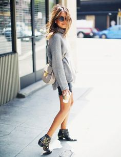 A gray turtleneck is worn with a black miniskirt, a Chloé Drew Bag and black booties with gold detail.