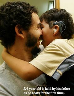 A 6-year-old is held by his father as he hears for the first time.  -Northgate Hearing Services