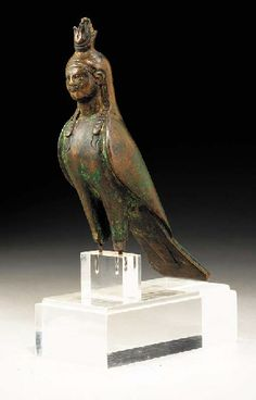 AN EGYPTIAN BRONZE BA-BIRD   Roman Period, Circa 2nd Century A.D.   The falcon body with a human head and face, the lappets of a nemes-headdress falling on to the chest revealing incised strands of long curly hair, wearing a composite crown framed by cow's horns  4 7/8 in. (12.4 cm) high
