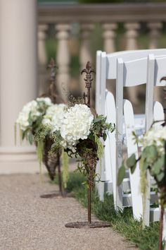 Aisles decorated with white hydrangeas, seeded eucalyptus, and amaranthus arranged in grapevine cones on brass stands.