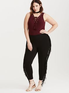 """The ultimate layering piece - the bodysuit - gets an upgrade in our exclusive Torrid Insider Collection. Made with a sumptuous, silky-soft and stretchy burgundy knit, the secured snap button closure design brings sexy back to the front with a lace up tie neck detailed with gold tone grommets.<div><br></div><div><b>Model is 5'9.5"""", size 1<br></b><div><ul><li style=""""list-style-position: i..."""
