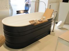 Is this custom fabricated, or is it actually a painted stock tank? Black and white tub, wood backrest and bath shelf. Modern faucet, floor mounted.