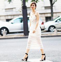 Jeanne Damas wears a white slip midi dress and black heels