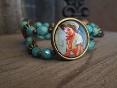 3 vintage cowgirls featured on this fun and sassy bracelet are highlighted with double strands faceted glass turquoise colored beads.  Small brass beads add an additional accent to this fun bracelet.   The stretch bracelet will fit an average wrist size comfortably.  To view all of our beauti...