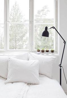 Makuuhuoneen ikkunoista avautuu näyttävä metsämaisema. Sängyssä on Annon valkoiset pellavalakanat ja ikkunalaudalla koreilee rivistö Pian ja Jennan tekemiä pieniä keramiikkakuppeja.