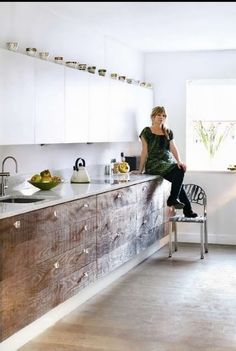 A cute relaxed kitchen with reclaimed timber lower cabinet drawers, timber floors and modern white upper cabinets
