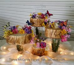Woodlands wedding cake. Fowers and butterflies accent this tree bark looking cake. #tonyascakes.com